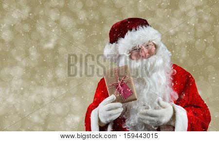 Santa Claus holding a plain brown wrapped package. The eco friendly recyclable gift is tied with string and has a blank gift tag. On a light gold bokeh background.