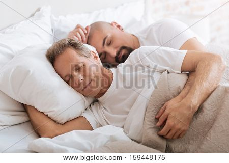 We dreaming together. Cheerful positive delighted gay couple lying on the bed in the bedroom while expressing love and care and sleeping together