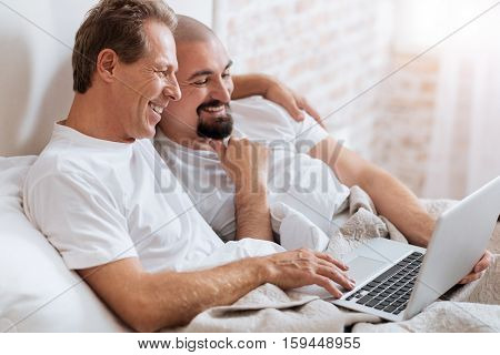 We amusing together. Happy delighted positive homosexual couple lying in the bed in the bedroom while expressing love and care and surfing the Internet using the laptop