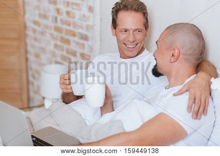 I love you. Happy delighted cheerful non-traditional couple lying in the bed in the bedroom and using the laptop while drinking tea and hugging