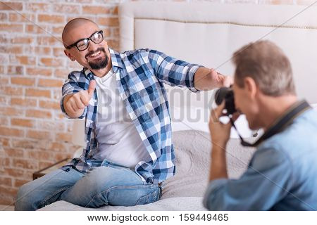 Full of delight. Delighted joyful cheerful homosexual man sitting on the bed and posing while smiling and his partner taking the picture of him