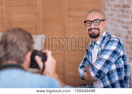 Smiling for a portrait. Happy joyful cheerful man sitting in the studio and posing while being with crossed arms and the photographer taking the picture of him