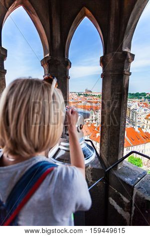A young woman stands on top of the clock tower and looks at the Old Town in Prague using a telescope.