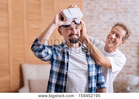 We like modern technologies. Smiling joyful delighted non-traditional couple standing at home and testing virtual reality glasses while expressing care and interest