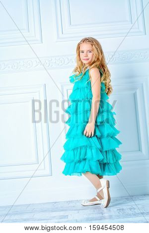Fashion concept. Pretty eight year old girl in beautiful evening dress posing in a room with classic white interior. Kid's fashion.