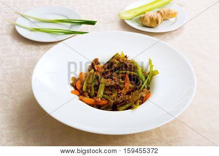 Meat Fried With Vegetables On The Plate Standing On The Table