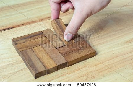 Hand-picked pieces of wooden blocks to complete metaphor for unity the key to success.