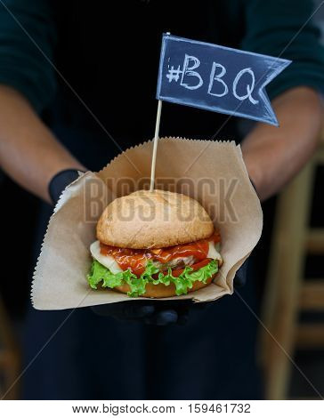 Fresh burger cooked at barbecue outdoors. Cookout american bbq with text flag. Big hamburger with steak meat and vegetables closeup with chef unfocused at background. Street food, fast food.