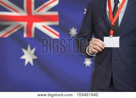Businessman Holding Name Card Badge On A Lanyard With A National Flag On Background - Australia