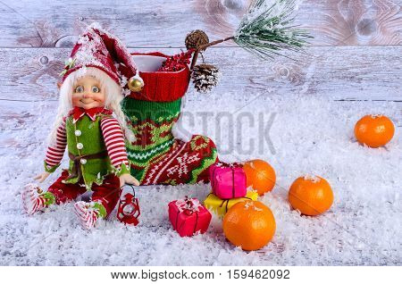 Christmas scene with elf Christmas socks tangerines and gifts. On a light background.