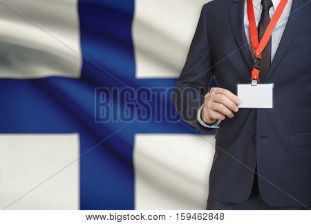 Businessman Holding Name Card Badge On A Lanyard With A National Flag On Background - Finland