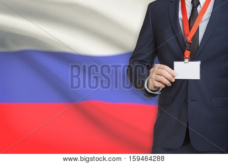 Businessman Holding Name Card Badge On A Lanyard With A National Flag On Background - Russia