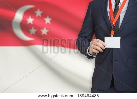 Businessman Holding Name Card Badge On A Lanyard With A National Flag On Background - Singapore