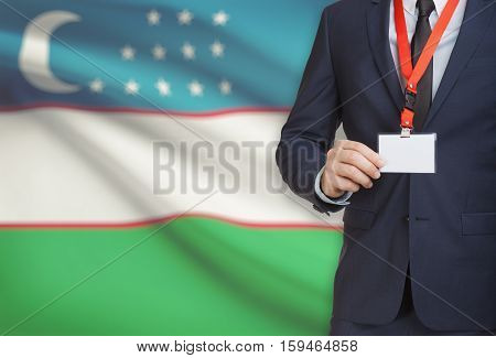 Businessman Holding Name Card Badge On A Lanyard With A National Flag On Background - Uzbekistan