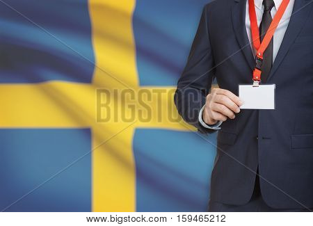 Businessman Holding Name Card Badge On A Lanyard With A National Flag On Background - Sweden