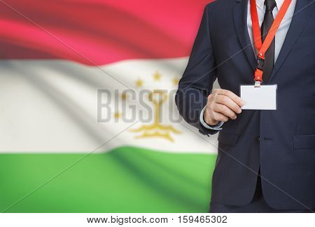 Businessman Holding Name Card Badge On A Lanyard With A National Flag On Background - Tajikistan