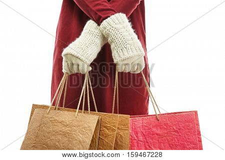 Female hands in mittens holding bags for Christmas shopping on white background