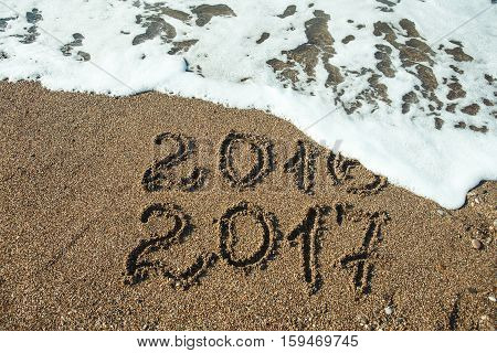 The Numbers 2017 on beach. New year holiday concept .
