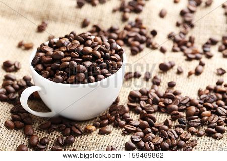 Brown Roasted Coffee Beans In Cup On Sackcloth