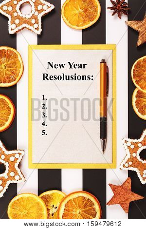 List of New Year goals. Christmas and new year holiday frame, made with stars, dried oranges, ginger snaps and spices on black and white background with lines.