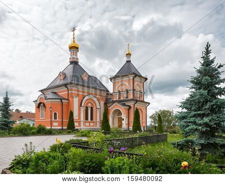 A beautiful Orthodox temple located on a hill surrounded by flowers and plants: arborvitae blue spruce shrubs.