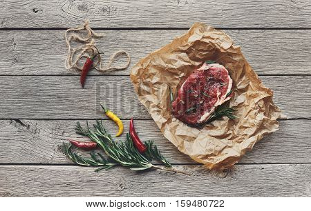 Raw beef steak in craft paper on dark wooden table background, top view. Fresh juicy meat, rosemary and chili peppers. Cooking ingredients, butcher's and grocery concept. Filtered image