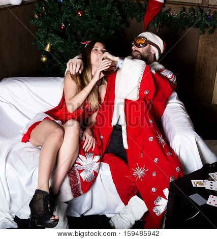 drunk santa claus with female nurse sexy woman in carnival costume drinking brandy.