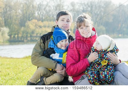 Family members portrait of parents with two sibling children in park