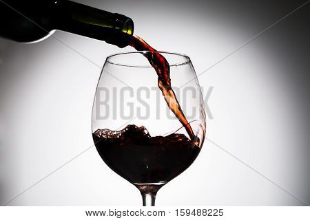 From bottle of green glass pouring wine into wine glass on blank background