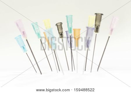 Colorful Needles without needle sheath put on white board.