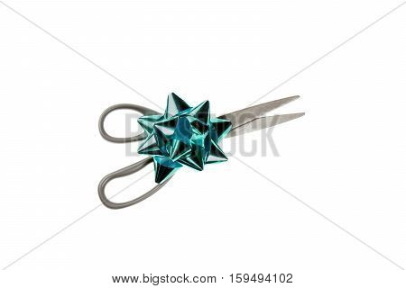 A pair of scissors and a green Christmas bow.