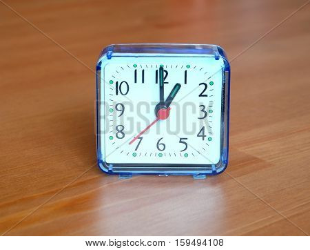 Square table clock showing one o'clock on wooden background closeup