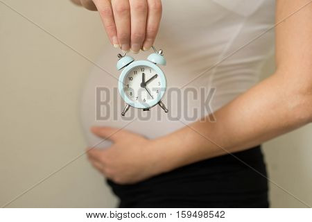 Pregnant woman holding alarm clock isolated on a white background.Concept of pregnancy.