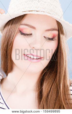 Woman face colorful eye makeup closed eyes straw hat on head smiling having fun closeup. Summer fashion studio shot on blue