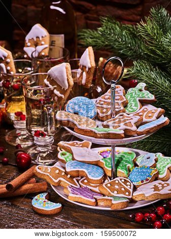 Christmas gingerbread cookies on Tiered Cookie Stand and white bottle wine. Group glass mug with handle on Wooden table . Christmas tree and Christmas ball background .