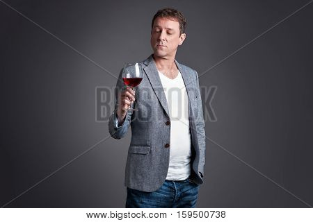 A middle age man holding and looking at a glass of wine