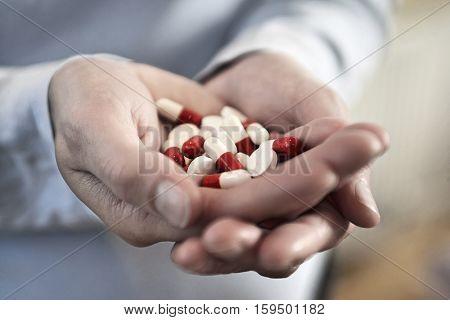 Closeup of woman's hands holding medicine pills