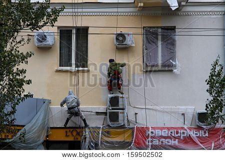 Volgograd Russia - November 02 2015: Builder worker painting facade of building house in Volgograd