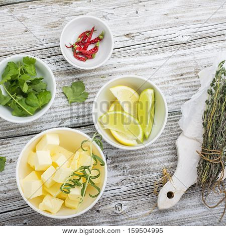 Ingredients Butter with thyme and rosemary and lemon zest. Sliced on a wooden board with herbs. selective Focus