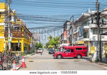 CHIANG MAI, THAILAND - FEBRUARY 3, 2016: Iconic traditional red truck taxi roaming the streets of Chiang Mai. Chiang Mai is a major tourist destination in northern Thailand.