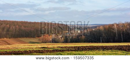 Autumn landscape . Fields, forest, village on hilly terrain. Beautiful blue sky with clouds.