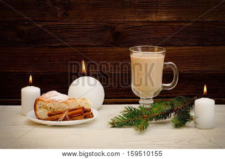 New Year`s mood apple pie cappuccino and spruce twigs on a wooden background