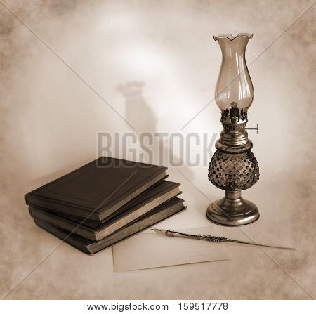 Blank paper card oil lamp and inkwell with a dip pen as a concept of writing letters and greetings on holidays. Photo in sepia tone.