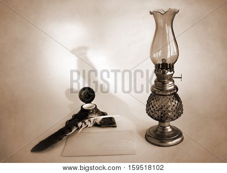 Blank paper card oil lamp and inkwell with a quill pen as a concept of writing letters and greetings on holidays. Photo in sepia tone.