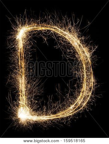 English big Letter D made from burning sparkles on black background. Shiny festive party firework font, latin alphabet text sign.