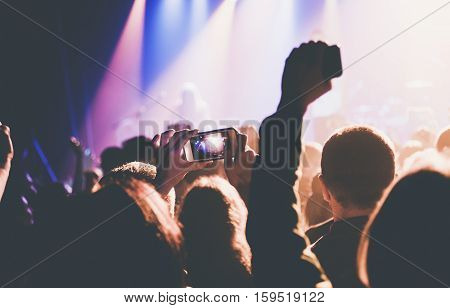 Female hands holding their smartphone and photographing concert.