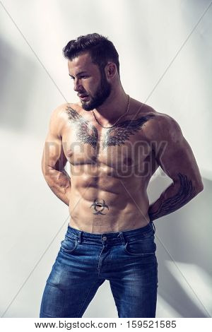 Handsome shirtless muscular man with jeans, standing, on light background