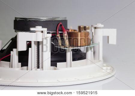 Copper wire coil on a white loudspeaker close view
