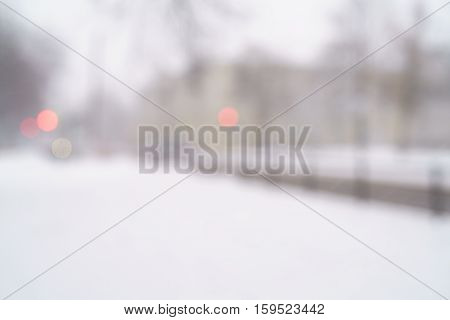 snowfall in town with blurred moving cars on background, blurred backdrop