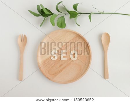 SEO ready meal, text seo on the wooden plate with spoon and fork , leaves, top view